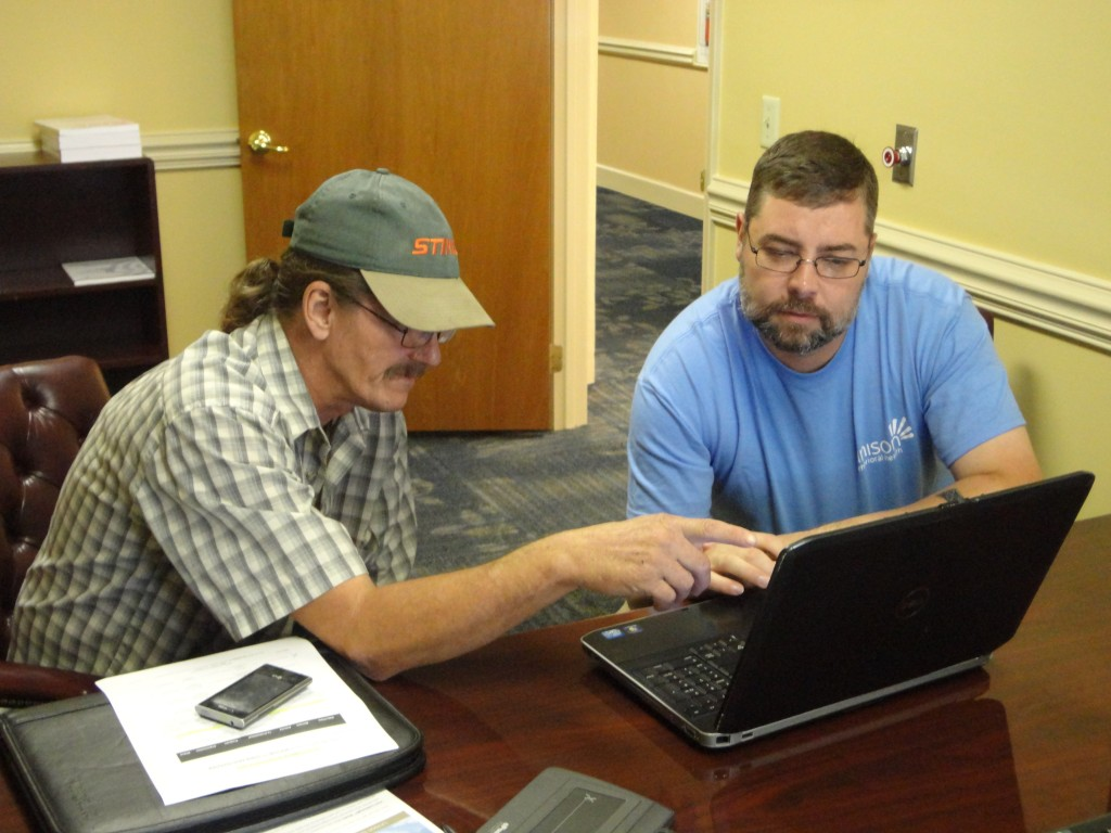 Jeffrey (left) showing his case manager Donald Holland how he's set up myStrength to send him encouragement and supportive alerts at times of the day he's most likely to experience depression. Photo credit: Unison.